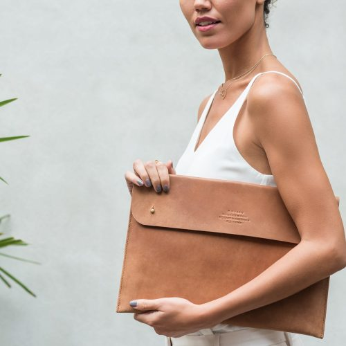 girl holding brown ethical leather laptop case
